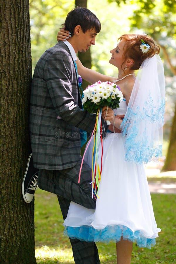 Lyckliga par som kramar och ler sig på trädet arkivbilder