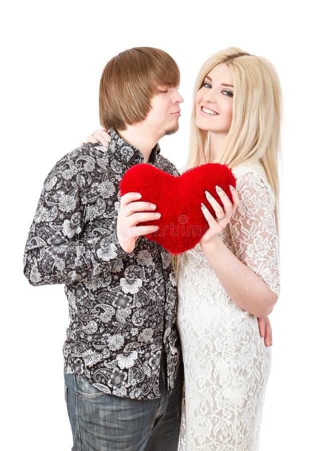 Lyckliga par som kysser och rymmer röda valentin hjärta royaltyfri bild