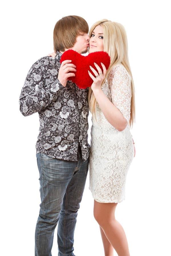 Lyckliga par som kysser och rymmer röda valentin hjärta royaltyfri fotografi