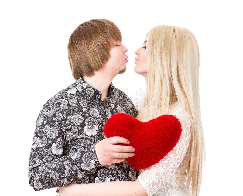 Lyckliga par som kysser och rymmer röda valentin hjärta royaltyfria bilder