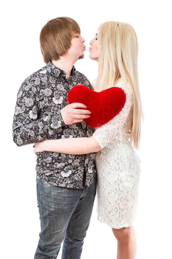Lyckliga par som kysser och rymmer röda valentin hjärta arkivfoto
