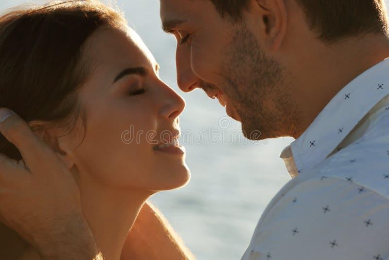 Lyckliga par som kysser på havsbakgrund arkivbilder