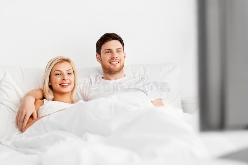 Lyckliga par som ligger i hemmastadd och hållande ögonen på tv för säng arkivfoton
