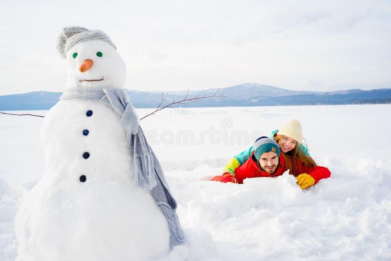 Lyckliga par som ligger i snow arkivfoto