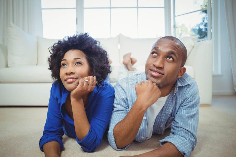 Lyckliga par som ligger på golvet royaltyfria bilder