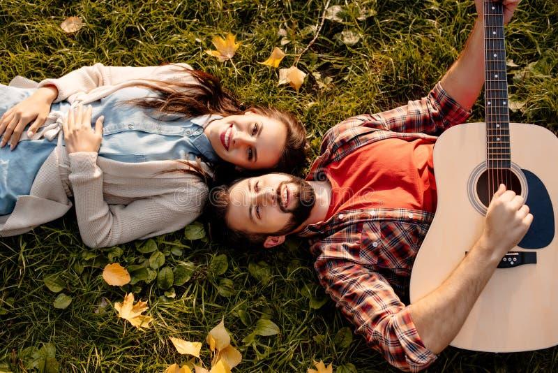 Lyckliga par som ligger på gräs i höst, parkerar medan pojkvännen royaltyfri foto