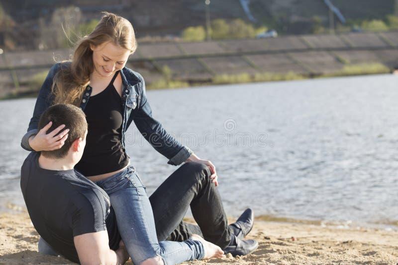Lyckliga par som ligger på stranden arkivbilder