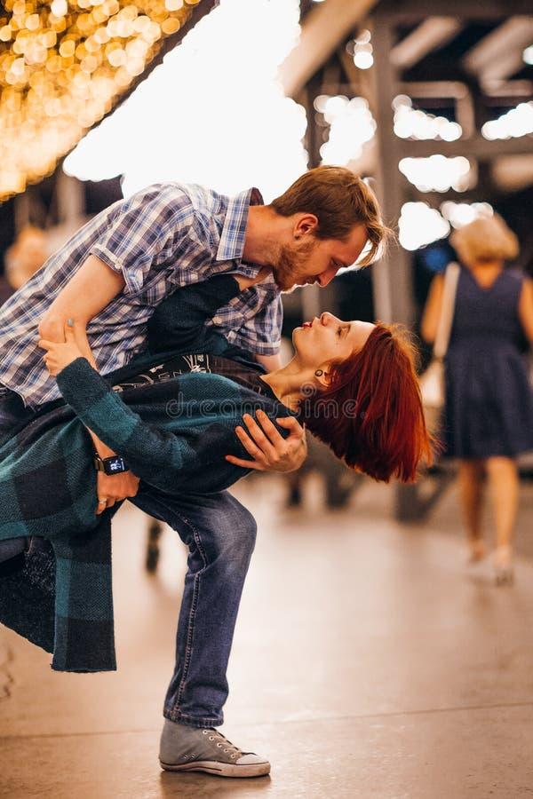 Lyckliga par som omfamnar i aftonen på ljusa girlander royaltyfri foto