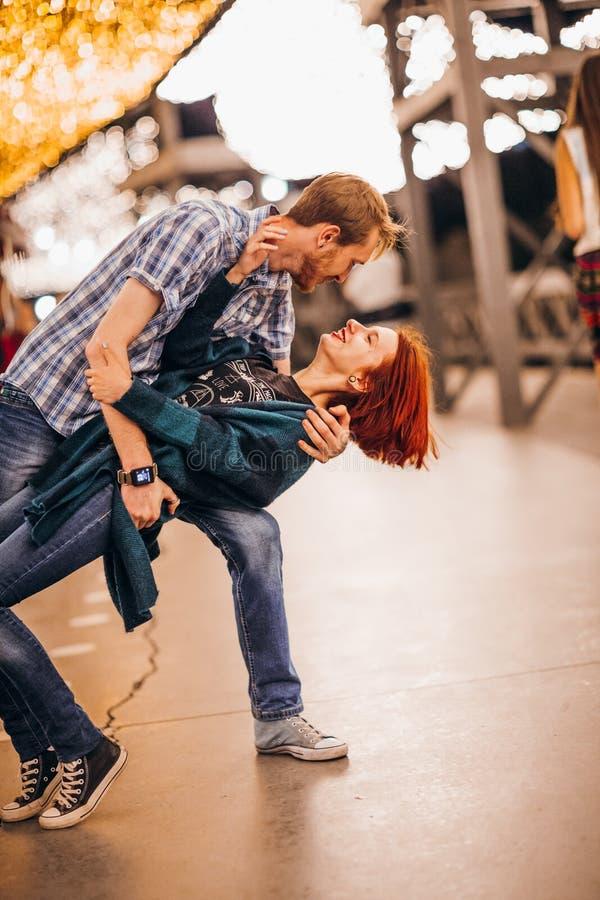 Lyckliga par som omfamnar i aftonen på ljusa girlander fotografering för bildbyråer