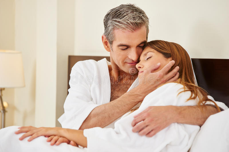 Lyckliga par som omfamnar i säng royaltyfria bilder