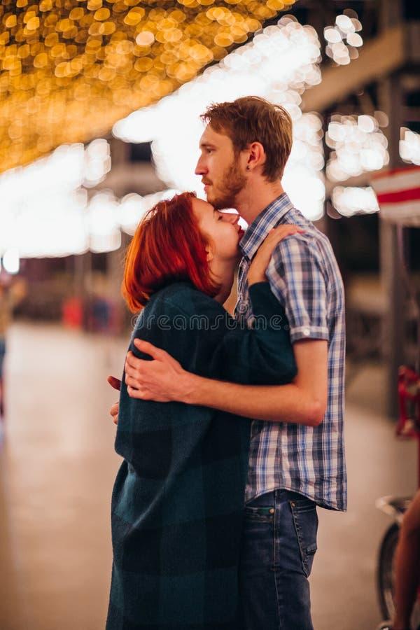 Lyckliga par som omfamnar och kysser i aftonen på ljusa girlander royaltyfria bilder
