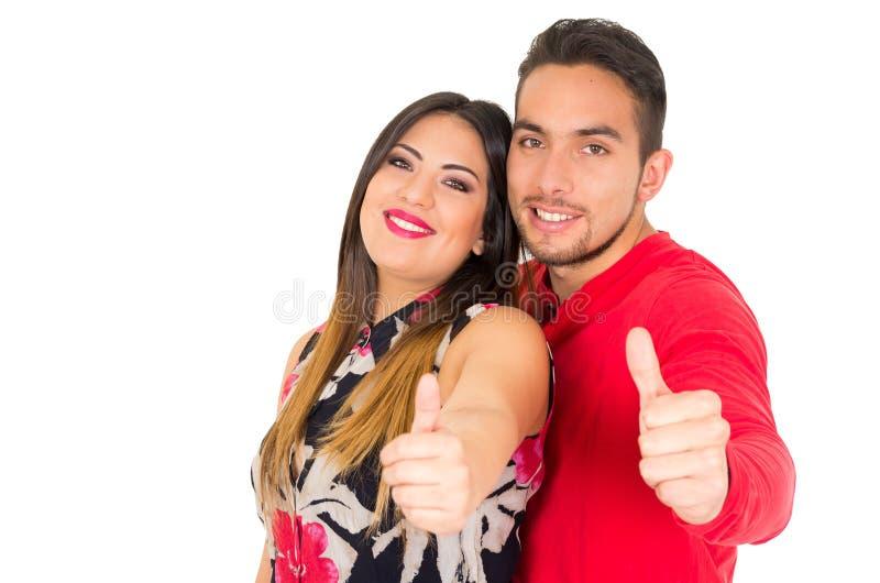 Lyckliga par som omfamnar och ser kameran, med tummar upp, på vit bakgrund arkivfoton