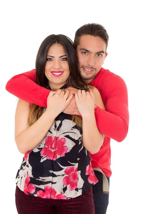Lyckliga par som omfamnar och ser kameran på vit bakgrund arkivfoton