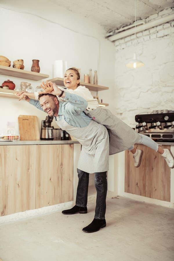 Lyckliga par som omkring bedrar i deras k?k royaltyfri fotografi