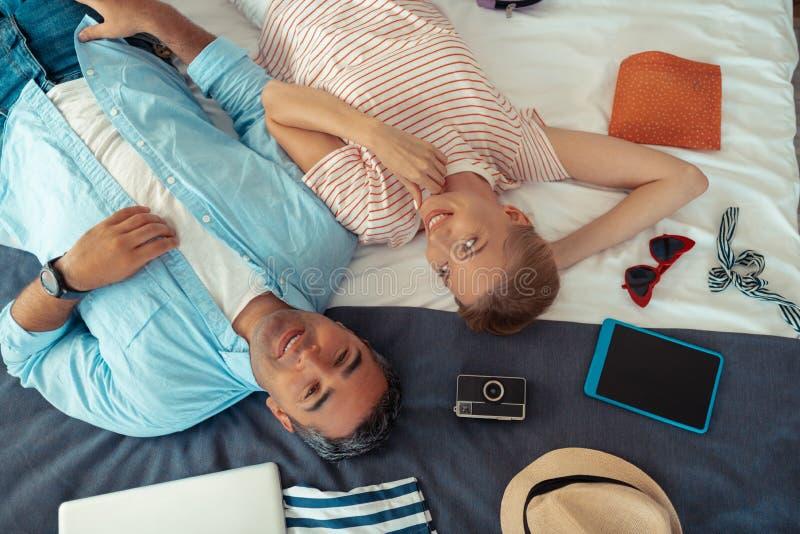 Lyckliga par som packar upp långsamt deras feriesaker fotografering för bildbyråer