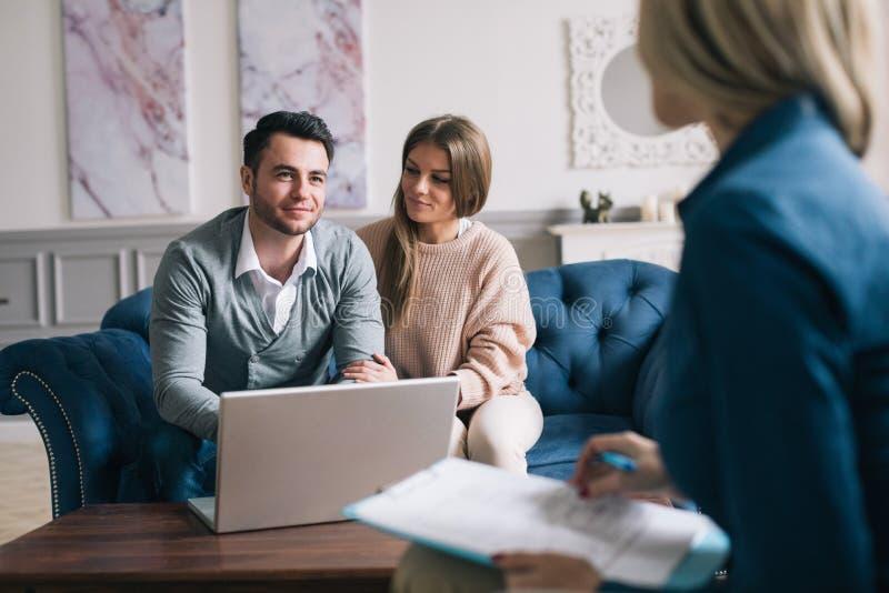 Lyckliga par som planerar deras framtid, medan konsultera med försäkringmedlet i deras hem royaltyfria foton
