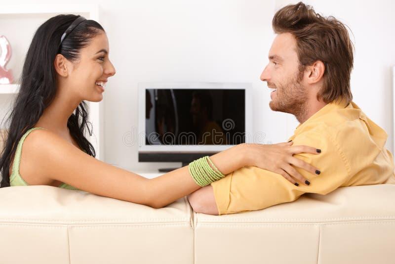 Lyckliga par som pratar på sofaen arkivfoton