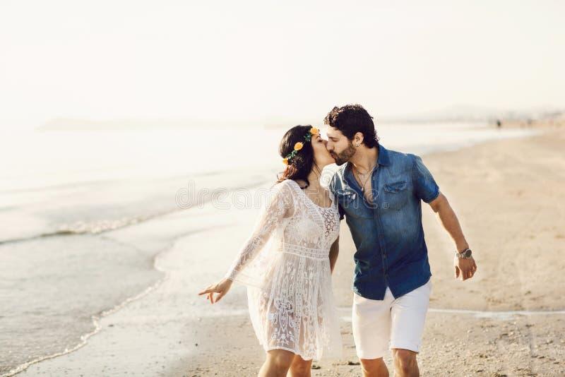 Lyckliga par som promenerar havet som rymmer händer Flickan har en blommakrans på hennes huvud k?rlekshistoria f?r tr?dg?rds- fli arkivbilder