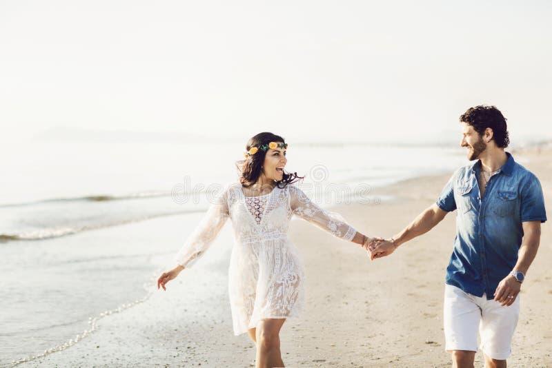 Lyckliga par som promenerar havet som rymmer händer Flickan har en blommakrans på hennes huvud k?rlekshistoria f?r tr?dg?rds- fli royaltyfria bilder