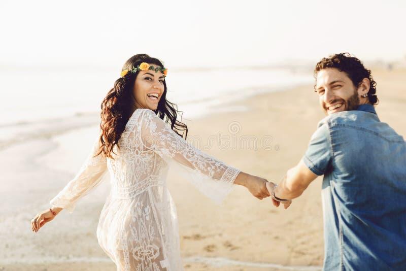 Lyckliga par som promenerar havet som rymmer händer Flickan har en blommakrans på hennes huvud k?rlekshistoria f?r tr?dg?rds- fli fotografering för bildbyråer