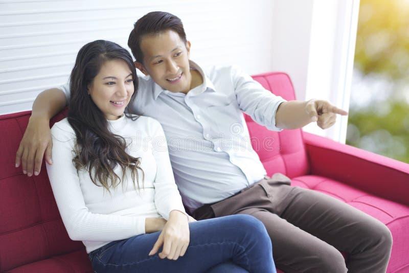 Lyckliga par som ?r f?r?lskade och tycker om h?lla ?gonen p? massmediainneh?llet som hemma kopplar av sammantr?de p? den r?da sof fotografering för bildbyråer