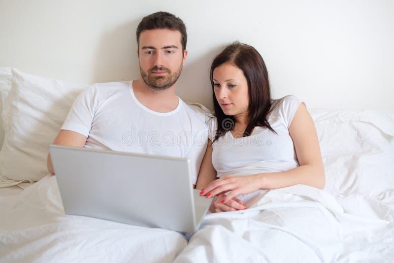 Lyckliga par som söker för konsumentupplysning i internet arkivfoto