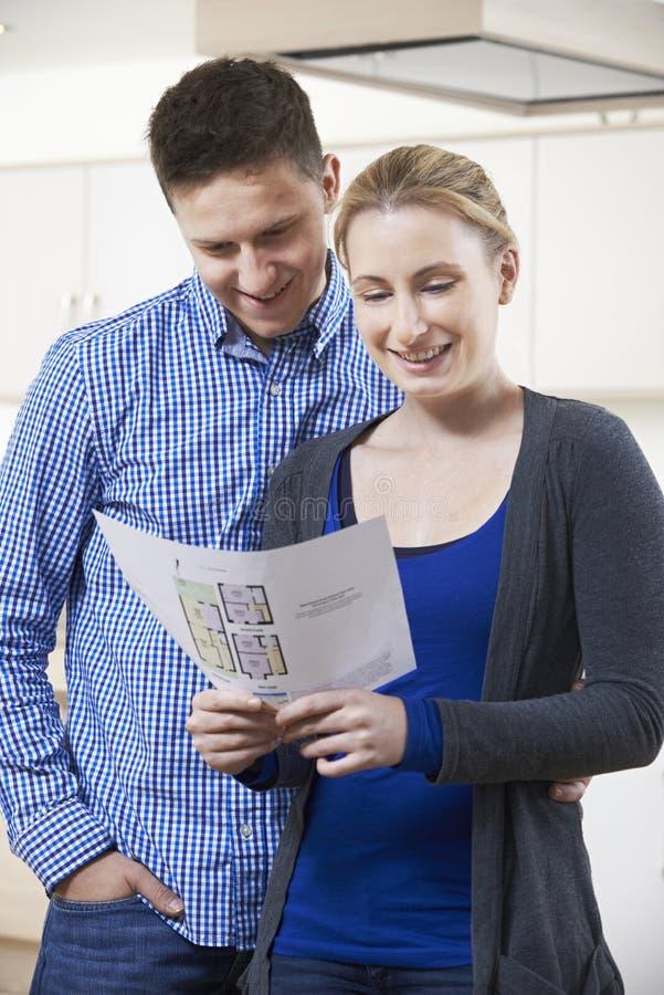 Lyckliga par som ser detaljer för egenskap som de hoppas för att köpa royaltyfri fotografi