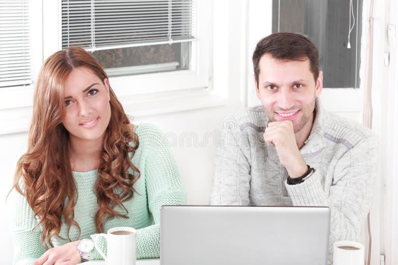 Lyckliga par som ser kameran med den hemmastadda bärbara datorn royaltyfri fotografi