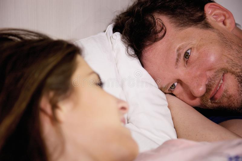 Lyckliga par som ser sig i förälskad closeup för säng royaltyfri foto