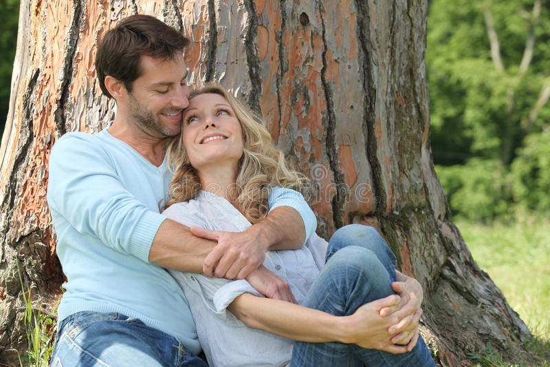 Lyckliga par som sitts av treen royaltyfria bilder
