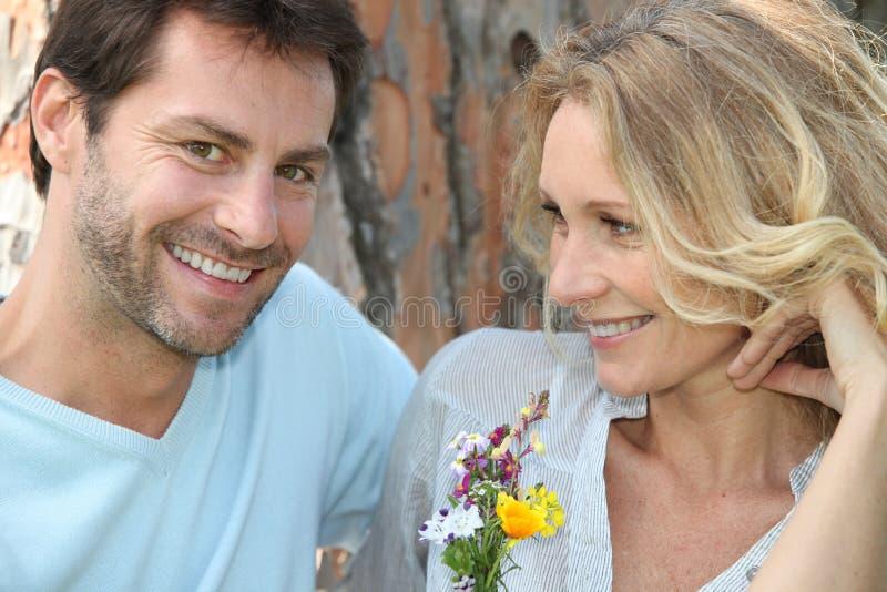 Lyckliga par som sitts av treen arkivbilder