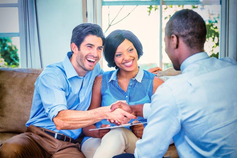 Lyckliga par som skakar händer med fastighetsmäklaren royaltyfria bilder