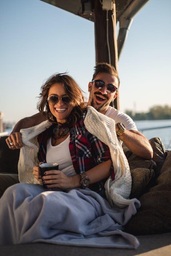 Lyckliga par som skrattar, medan dricka kaffe vid floden arkivfoto