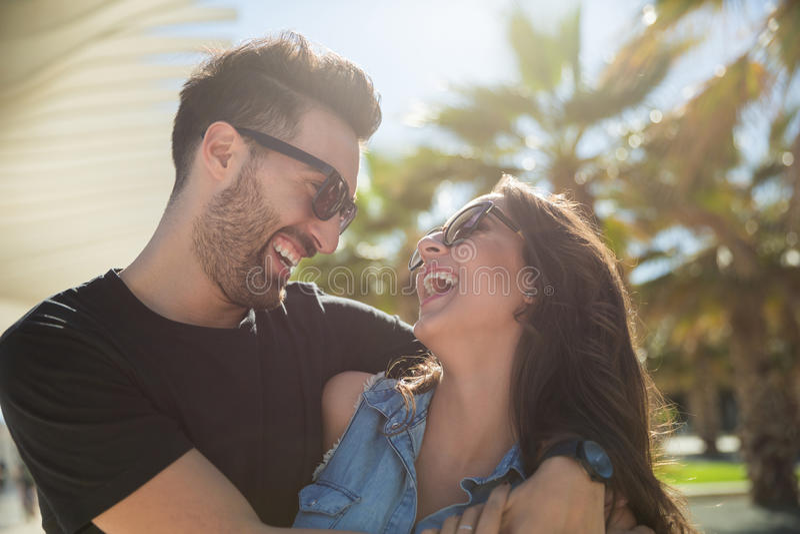 Lyckliga par som skrattar tillsammans att stå utanför royaltyfri bild