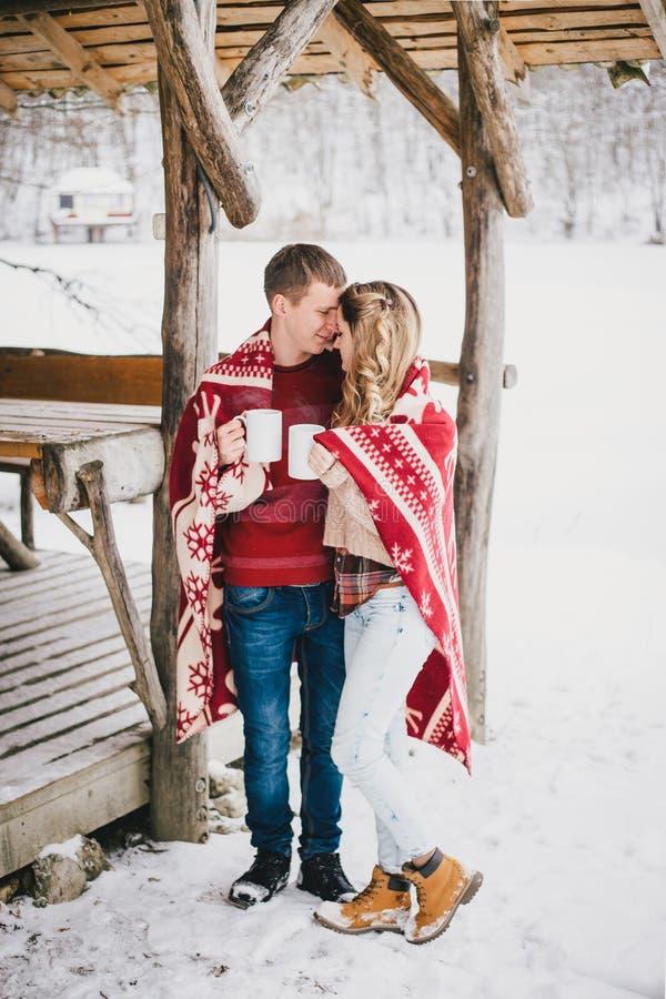 Lyckliga par som slås in i pläd, dricker varmt te i en snöig skog royaltyfria foton
