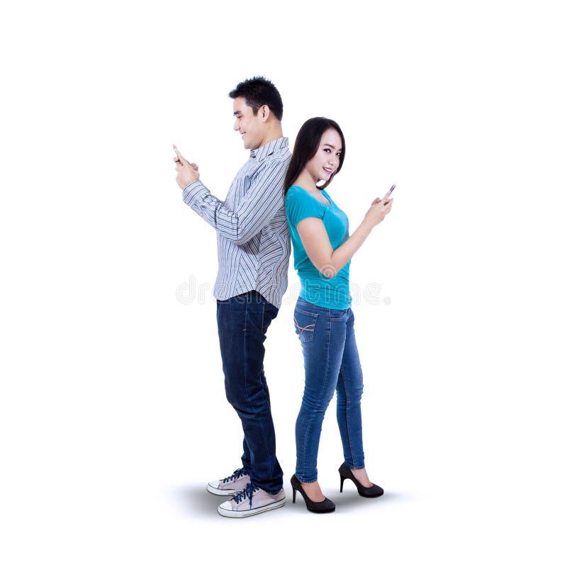 Lyckliga par som smsar med mobiltelefonen royaltyfri foto