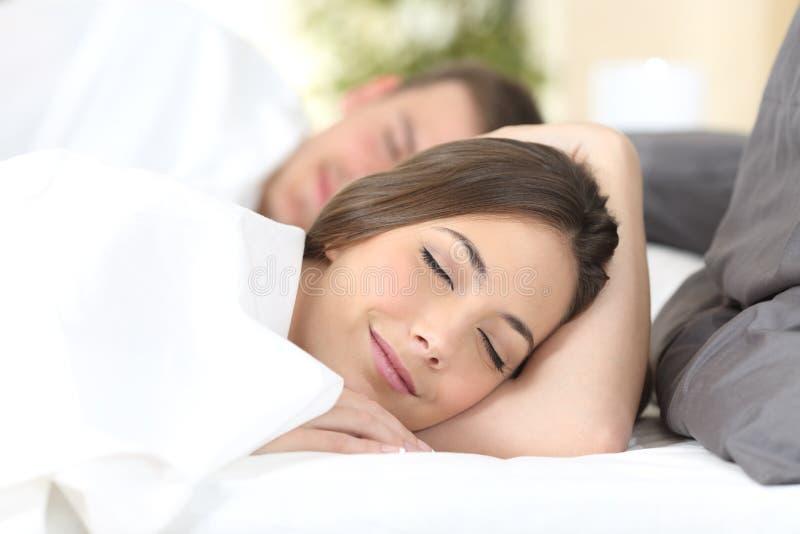 Lyckliga par som sover på en säng royaltyfri foto
