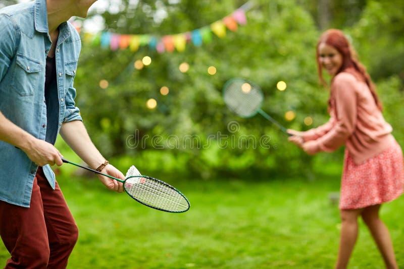 Lyckliga par som spelar badminton på sommarträdgården royaltyfri bild