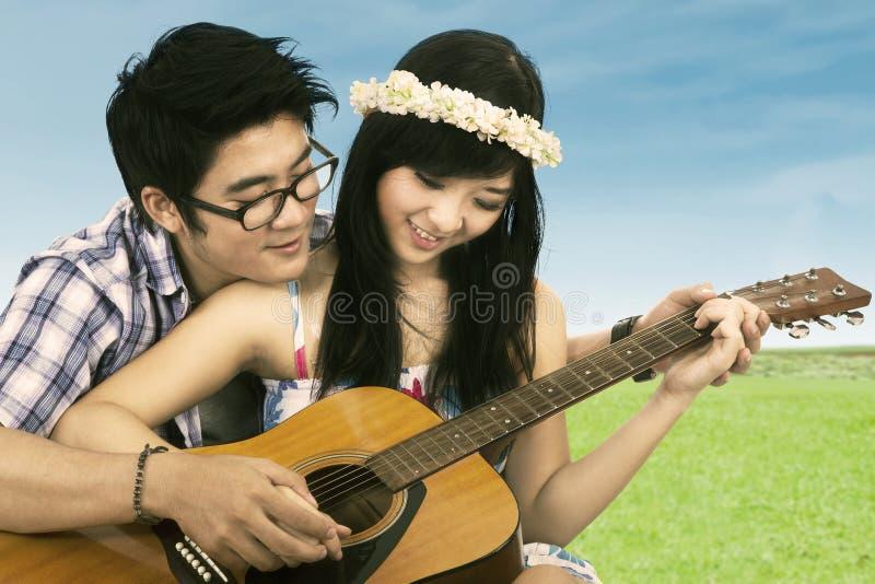 Lyckliga par som spelar gitarren royaltyfria bilder