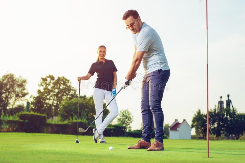Lyckliga par som spelar golf på klubban arkivfoton