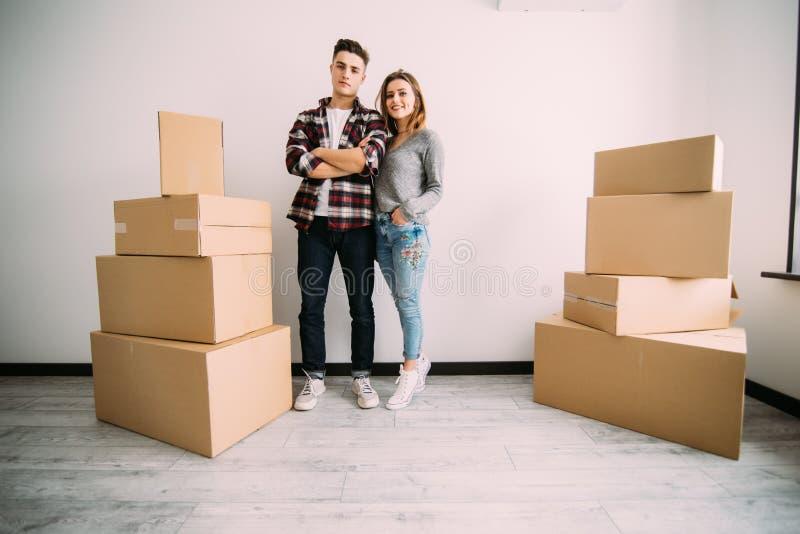 Lyckliga par som står nära askar i deras nya lägenhet Förflyttning och flyttning arkivbild