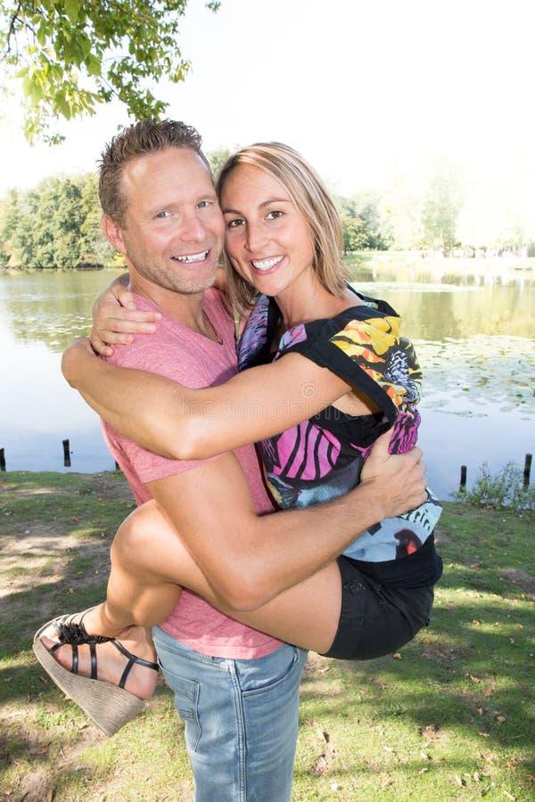 Lyckliga par som står skratta tillsammans i nära omfamning royaltyfria bilder