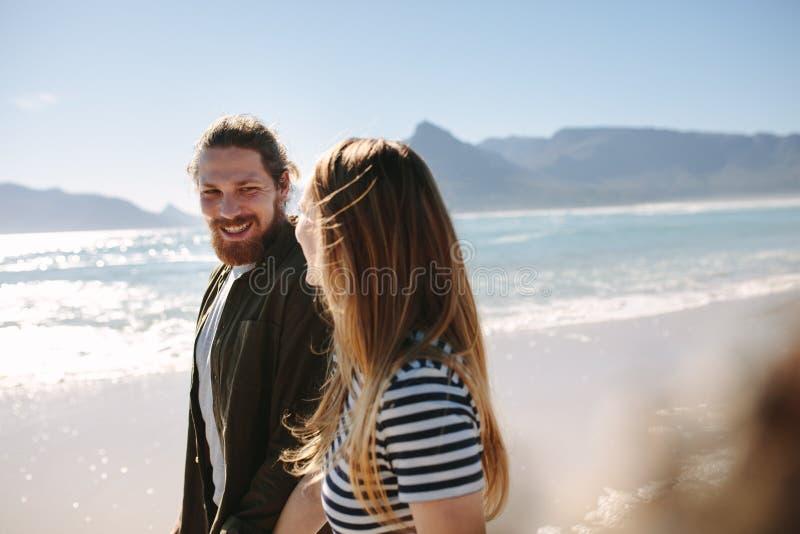 Lyckliga par som strosar på stranden royaltyfria bilder