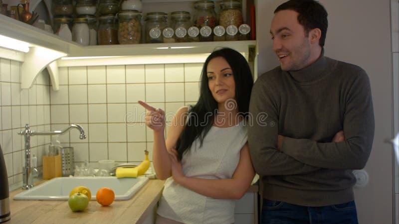 Lyckliga par som talar, medan laga mat i kök hemma royaltyfri foto