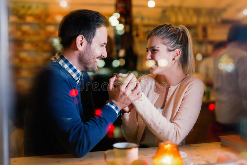 Lyckliga par som talar på stången och har datumet arkivfoton