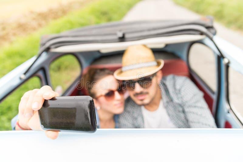Lyckliga par som tar en selfie på en tappningbil royaltyfria bilder