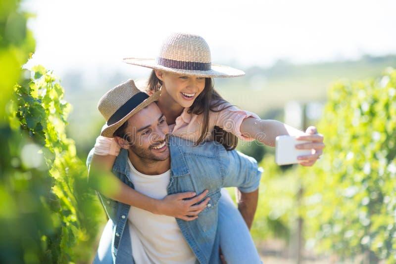 Lyckliga par som tar selfie, medan piggybacking på vingården arkivbilder