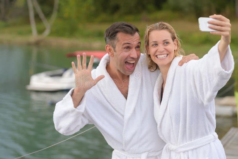 Lyckliga par som tar selfie mot härlig sikt med sjön royaltyfri foto