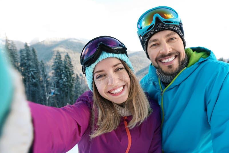 Lyckliga par som tar selfie under vintersemester arkivfoto