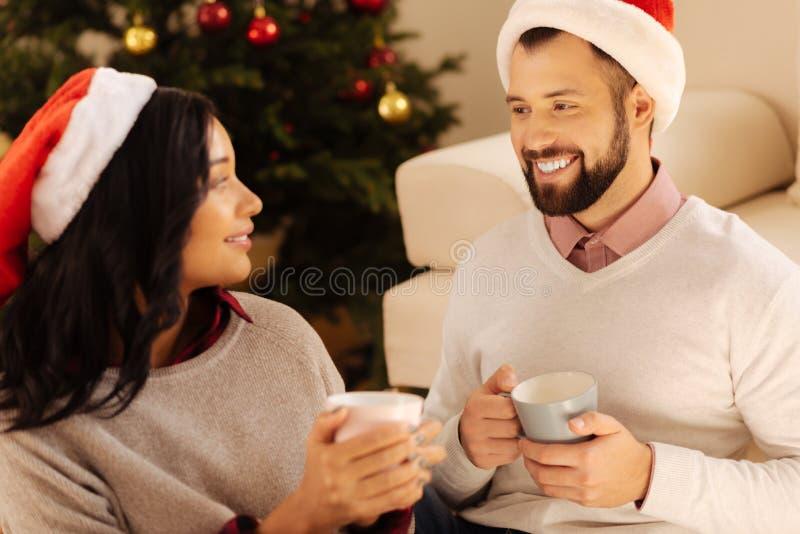 Lyckliga par som tillsammans dricker kaffe på julafton royaltyfri bild
